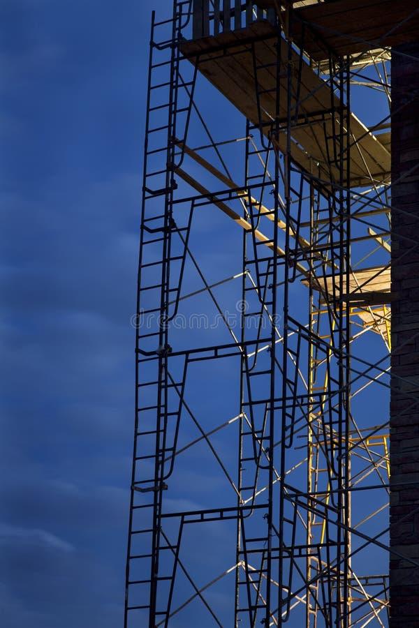 Andaime da construção de encontro ao céu do nighttime imagem de stock