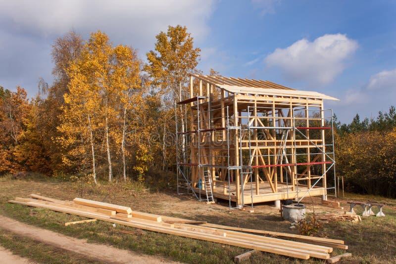 Andaime do metal em torno da casa inacabado Construção da casa ecológica Quadro de madeira da casa sob a construção imagem de stock