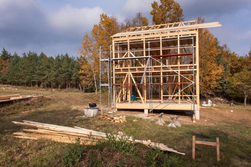 Andaime do metal em torno da casa inacabado Construção da casa ecológica Quadro de madeira da casa sob a construção fotos de stock royalty free