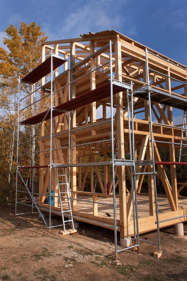 Andaime do metal em torno da casa inacabado Construção da casa ecológica Quadro de madeira da casa sob a construção imagens de stock