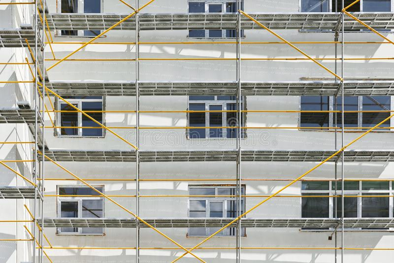 Andaime perto de uma casa nova sob a construção, a parede branca e a janela, tubulação amarela imagem de stock