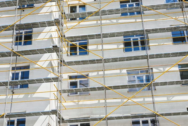 Andaime perto de uma casa nova sob a construção, a parede branca e a janela, tubulação amarela foto de stock royalty free