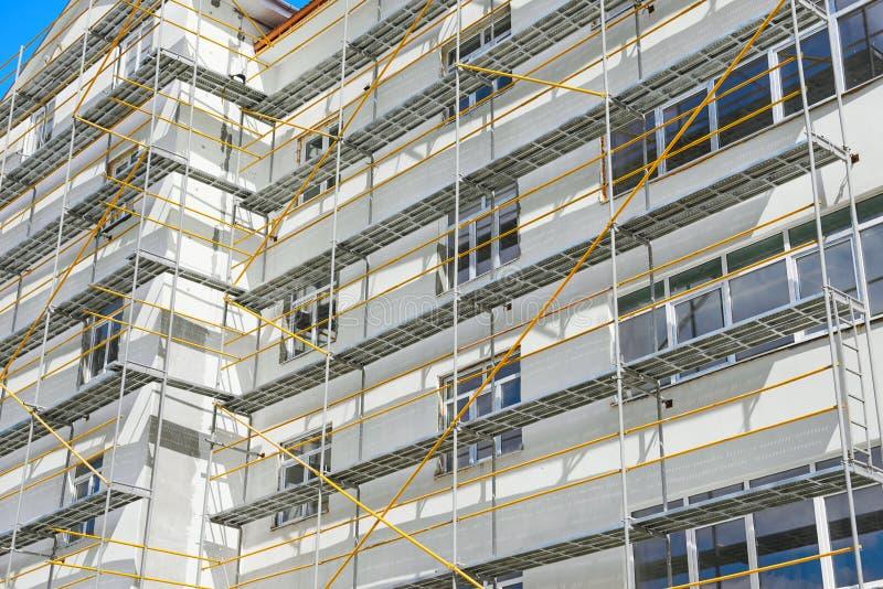 Andaime perto de uma casa nova, um exterior de construção, uma indústria da construção e do reparo, uma parede branca e uma janel foto de stock royalty free