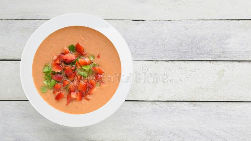 Andalusian gazpacho served in a white plate on a wooden table. Top view and empty copy space royalty free stock photos