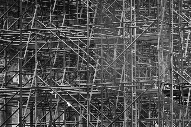 Andamio complicado que consiste en muchos polos y puntales dentro de un edificio histórico, blanco y negro imagen de archivo libre de regalías