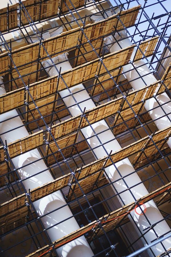 Andamio del metal con decking de madera construido alrededor de un edificio histórico con las columnas para la fachada del trabaj foto de archivo libre de regalías