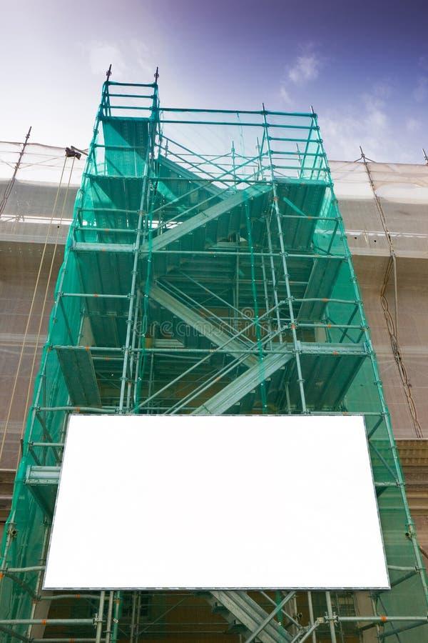 Andamio del metal, con los componentes prefabricados y la cartelera en blanco, trabajar en la fachada para la renovación de la pa imagenes de archivo