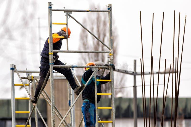 Andamio del metal de la estructura de dos trabajadores en emplazamiento de la obra foto de archivo libre de regalías