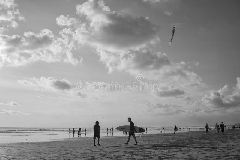 Andando com o surferboard da posse na praia de Kuta, Bali-Indonésia no tempo do por do sol imagens de stock