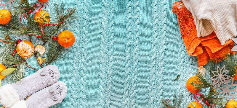 Andar de inverno com tangerinas, suéter de laranja, meias engraçadas e ramos de abeto em cobertor de malha azul Vista superior Co fotos de stock royalty free