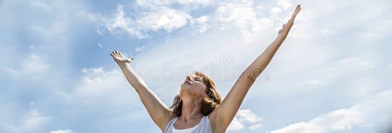 Andas den mellersta åldriga kvinnan för zenen som lyfter armar upp till, banret royaltyfria foton