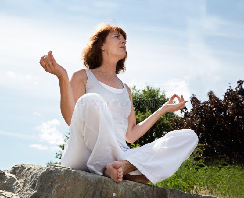 Andas den mogna kvinnan i yogaposition på en sten utomhus royaltyfria bilder