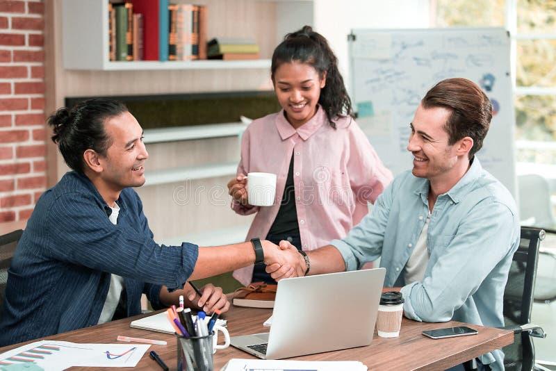 AndCaucasian Händedruck von zwei jungen asiatischen Geschäftsmännern glücklich achtern lizenzfreies stockbild