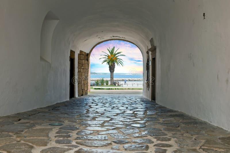Ande através de uma entrada medieval ao oceano em Lagos Portugal imagem de stock