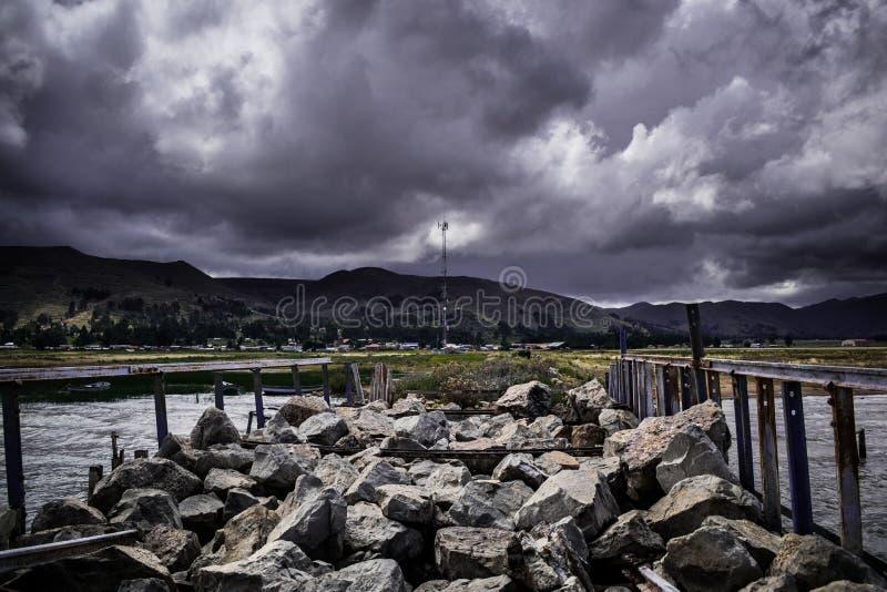 Andean mistic landskap p? en skeppsdocka i Titicaca sj?n med clowdy himlar och m?nga arkivfoton