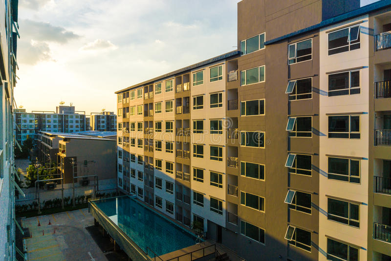 Andelslägenhetsolnedgång med lägenheter för nytt kvarter för swimmingpool moderna arkivfoton