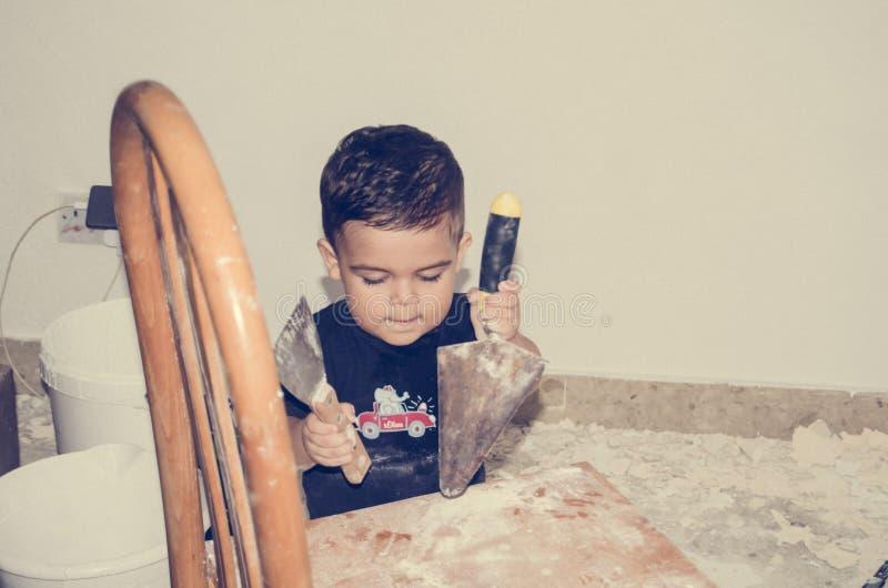Anderhalf éénjarigen baby het spelen met het schilderen van hulpmiddelen stock fotografie