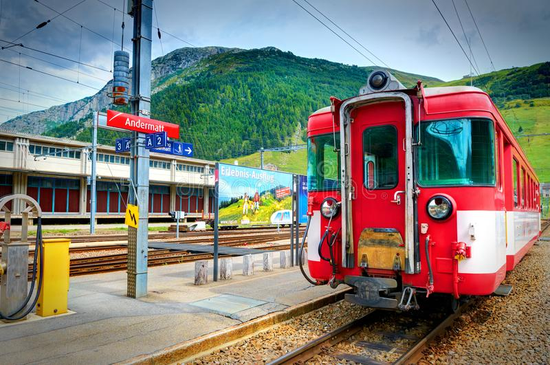 ANDERMATT, ШВЕЙЦАРИЯ, 19-ОЕ АВГУСТА 2010: Железнодорожный вокзал и гора ледника Bernina срочная тренируют красных тренеров пассаж стоковые изображения rf
