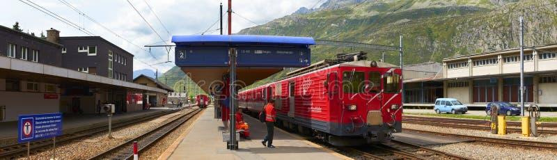 ANDERMATT, SUIZA, AGOSTO, 20, 2010: Opinión panorámica sobre el tren de pasajeros eléctrico de la montaña roja alpina suiza del f imagenes de archivo