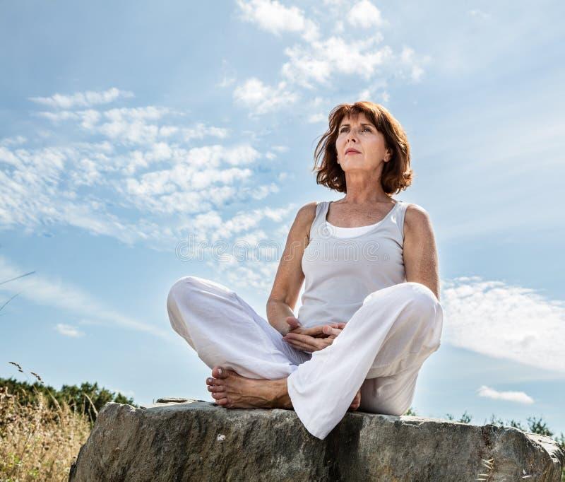 Andning för härlig mitt åldrades utomhus yogakvinnan fotografering för bildbyråer