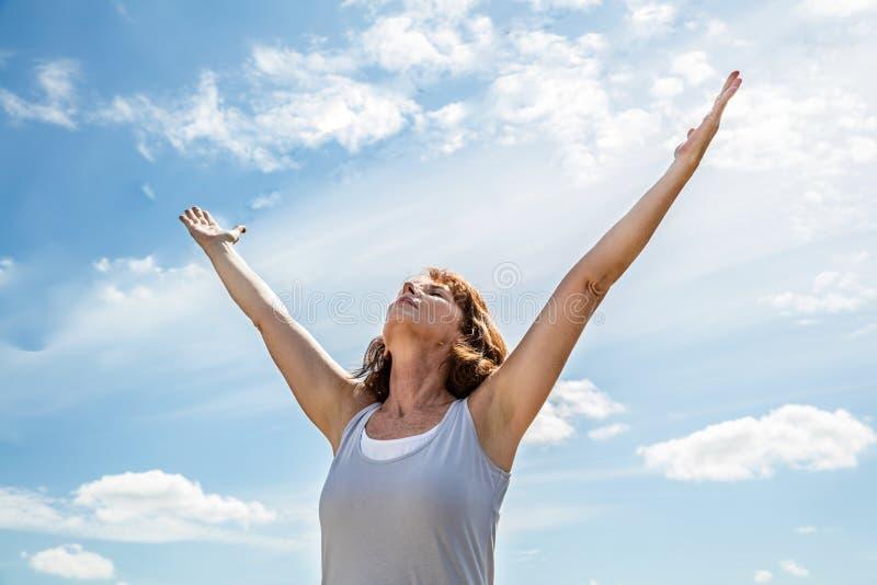 Andning utanför för zenyogakvinnan som lyfter henne armar arkivbilder