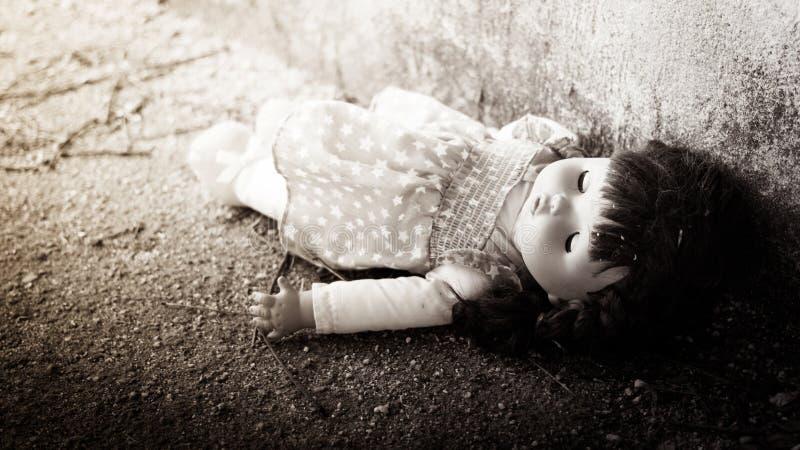 Andonedpersoon, Verlaten pop die op Vuile vloer, zwarte leggen en wh stock foto