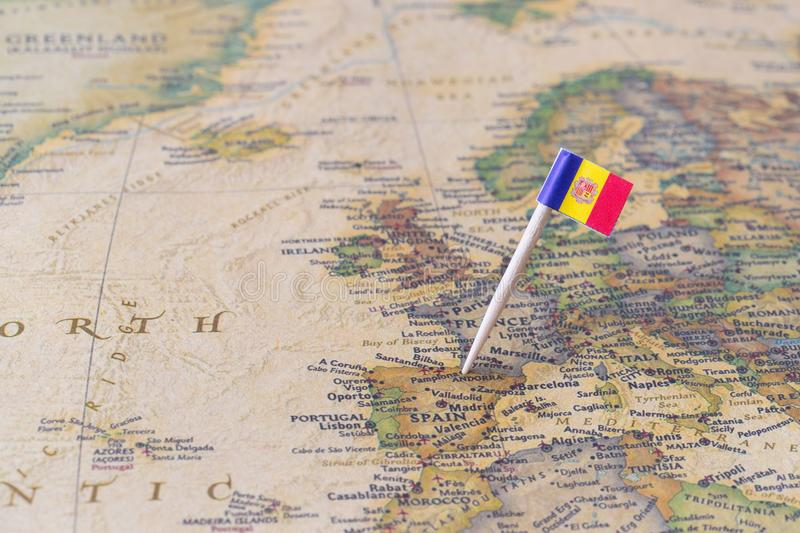 Andorra map and flag pin. Paper flag pin of Andorra on a world map showing neighboring countries. It is a sovereign landlocked microstate in Southwestern Europe royalty free stock images