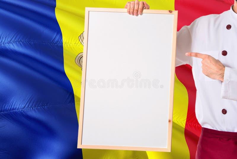 Andorrese Chef-kok die leeg whiteboardmenu op de vlagachtergrond van Andorra houden Kok die eenvormige richtende ruimte voor teks royalty-vrije stock afbeelding