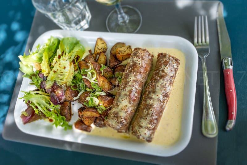 Andouillette, lyonnaise worst, Frans voedsel op blauwe achtergrond stock foto