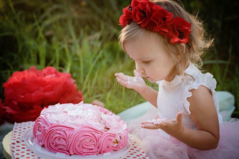 Andra f?delsedag av lilla flickan Två år gammal flicka som sitter nära berömgarneringar och äter hennes födelsedagkaka Kakadunder arkivfoton