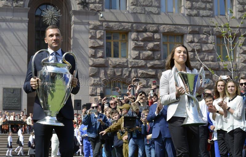 Andriy Shevchenko und Iya Andrushchak mit den Cups des Männer ` s und Frauen ` s der UEFA-Meister-Liga stockfotos