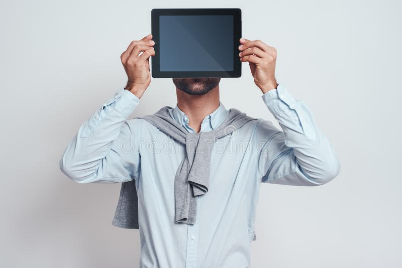Android. Bearded man in casual wear is holding his digital tablet in front of his face while standing against grey royalty free stock photography