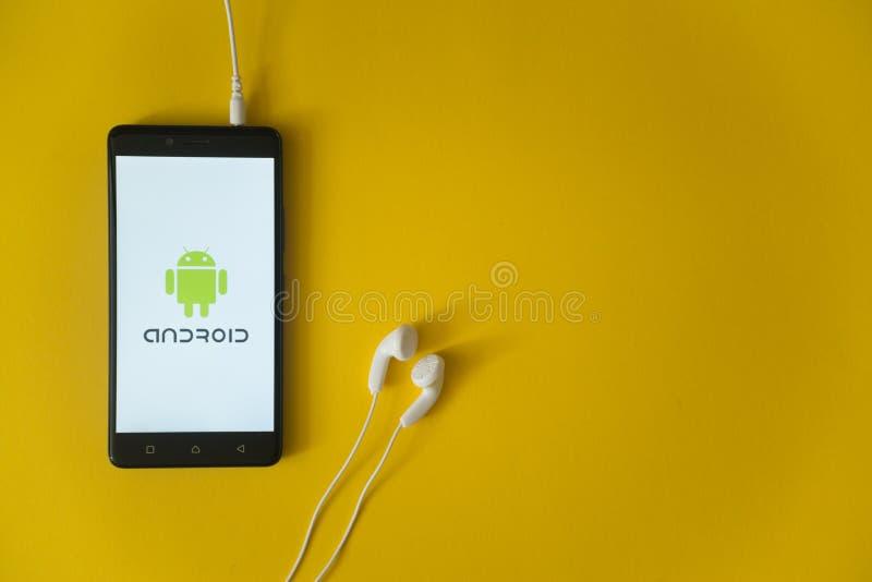 Android-embleem op het smartphonescherm op gele achtergrond royalty-vrije stock fotografie