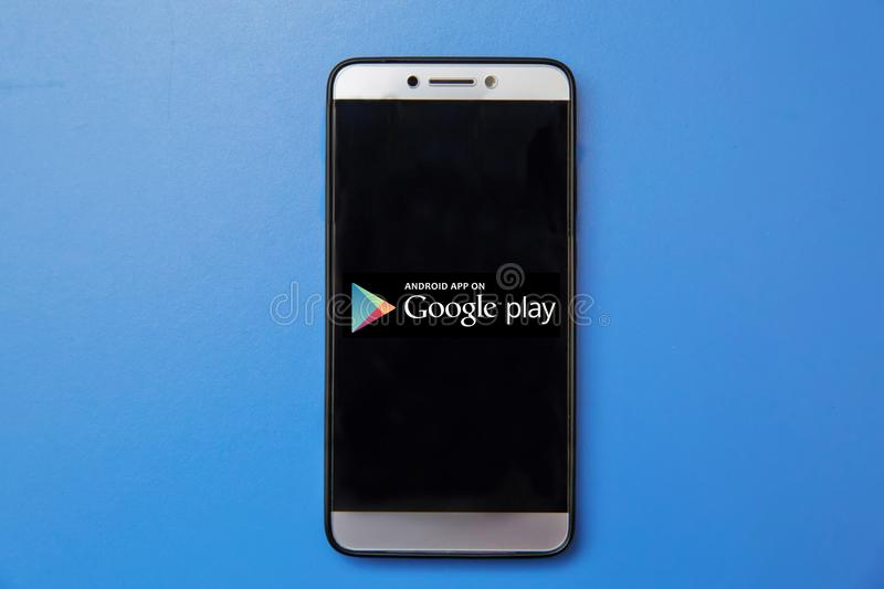 Android Google Play store logo on smartphone screen on blue background. Man holding smartphone with Android Google Play store logo stock photo