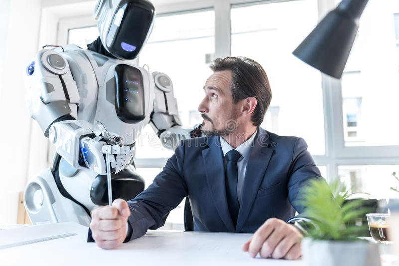 Android is standing near grumpy man stock image