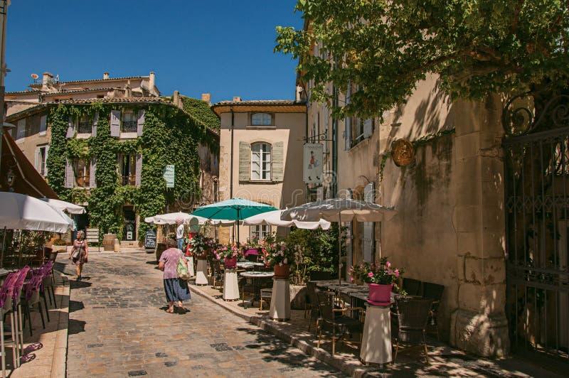 Andscape del callejón reservado con los restaurantes y de la gente en el centro de Lourmarin imagen de archivo