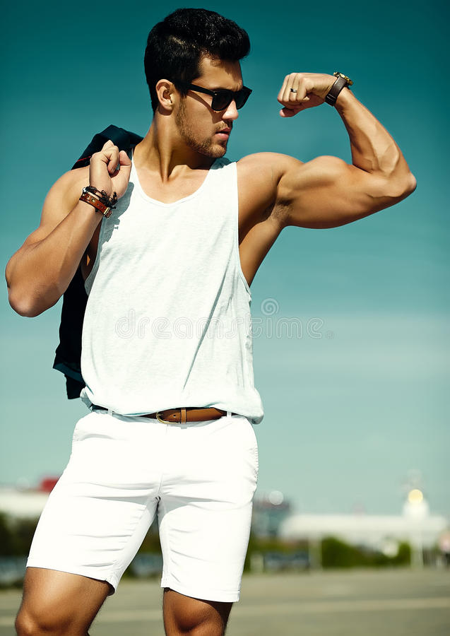 Andsome muscled model man in casual cloth in sunglasses in the street showing his muscles stock photography
