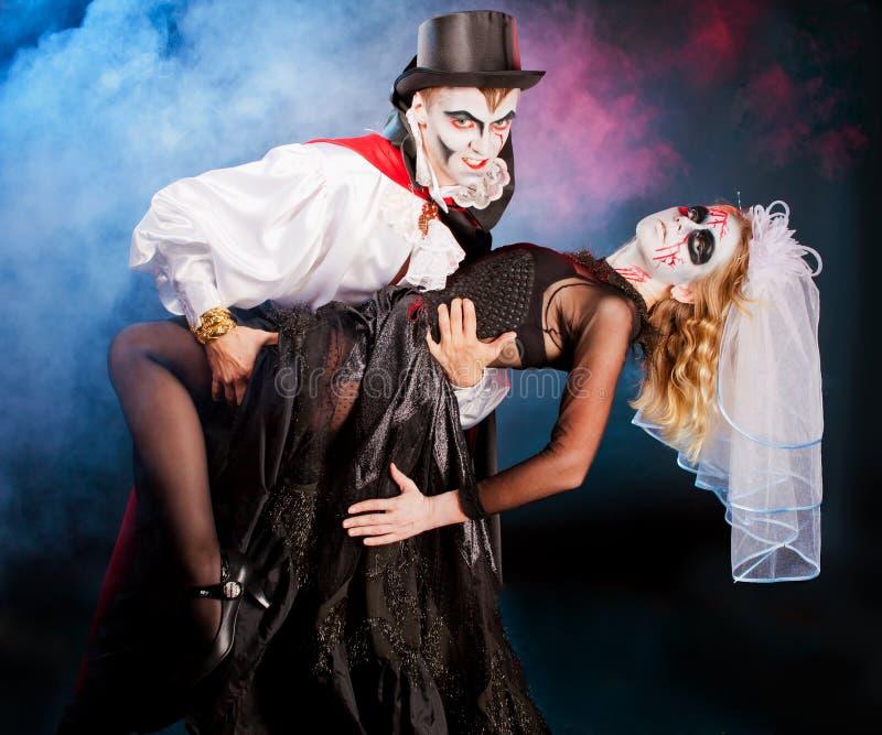 Andwoman del hombre que lleva como vampiro y bruja. Halloween imagenes de archivo
