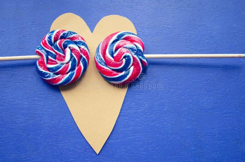 Andy-Strudelregenbogen ringsum zwei Lutscher auf Herz-förmigem Süßigkeitsstreifen auf einem Stock auf blauem Hintergrund Zu küsse stockbild