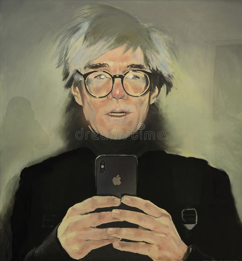 Andy Warhol. Artist Andy Warhol seems about to take a photo or a selfie with his cell phone. That could not have happened because the pop art world icon died stock photography