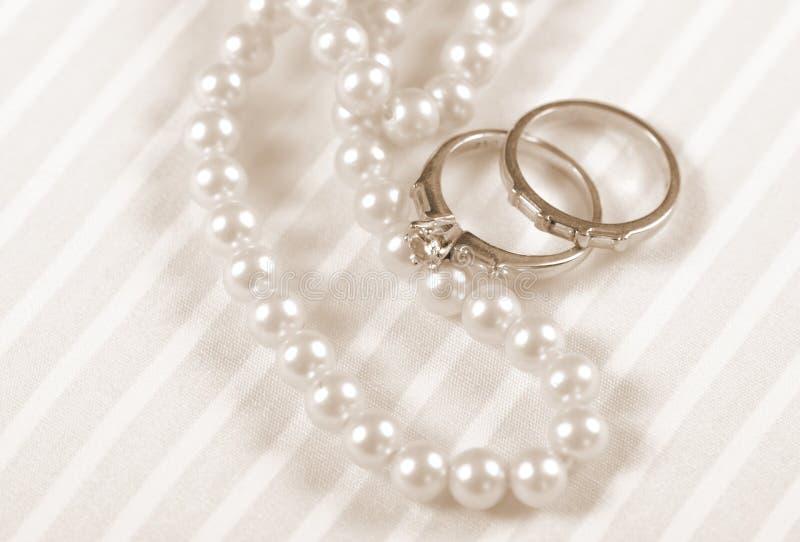 Aneis de noivado retros do casamento e do diamante do estilo do vintage do Sepia com colar da pérola fotos de stock royalty free