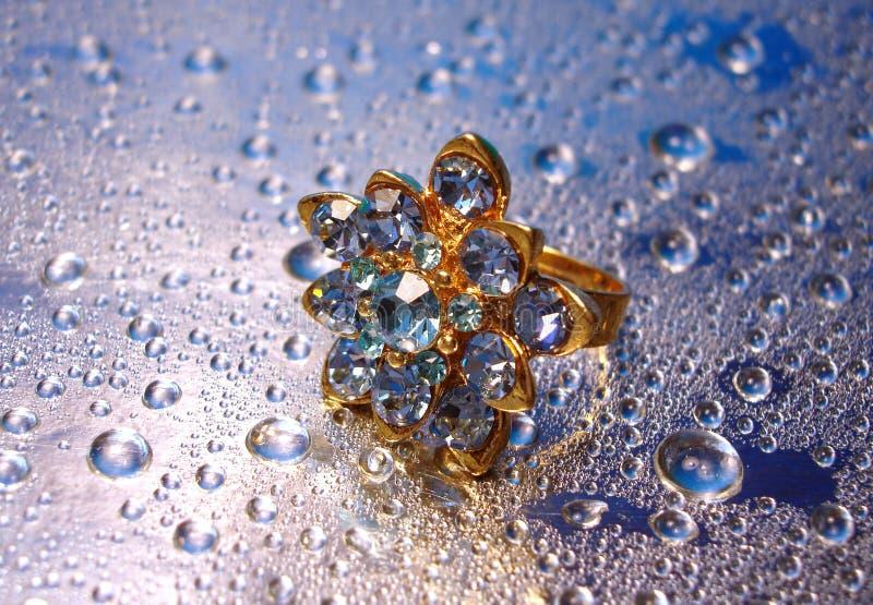 Anel azul bonito no fundo de prata com gota da água imagens de stock