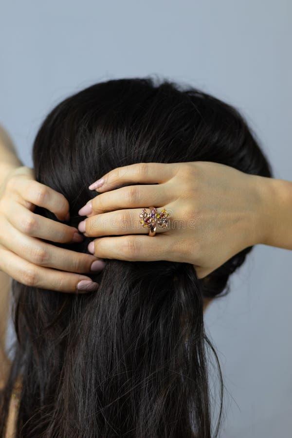 Anel bonito de pedras coloridas e ouro no dedo de uma mulher que toca em seu cabelo fotos de stock
