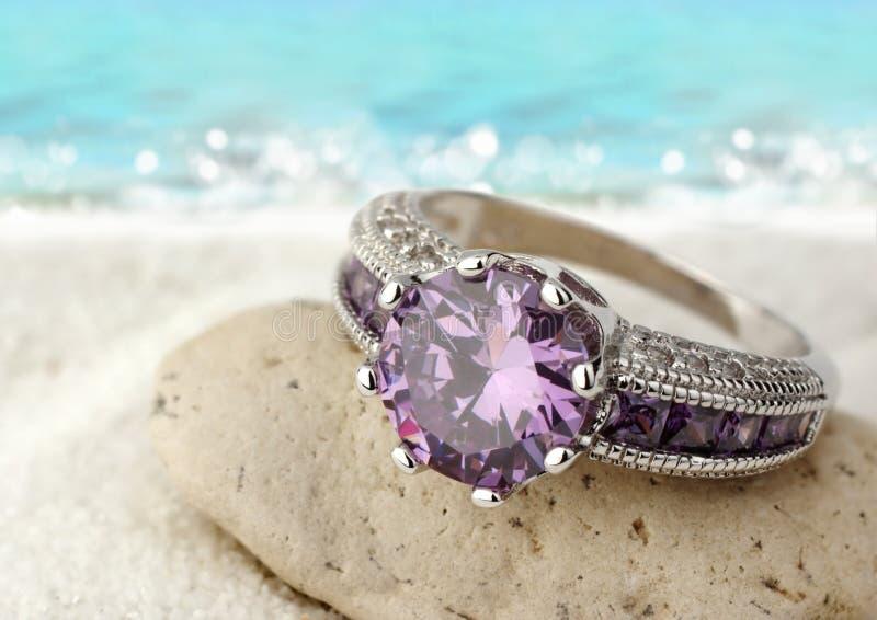Anel da joia com a pedra preciosa violeta na praia da areia com espaço da cópia imagens de stock