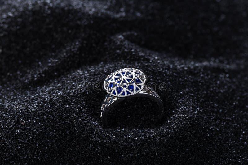 Anel da prata da forma do diamante com as pedras preciosas azuis na areia preta foto de stock royalty free