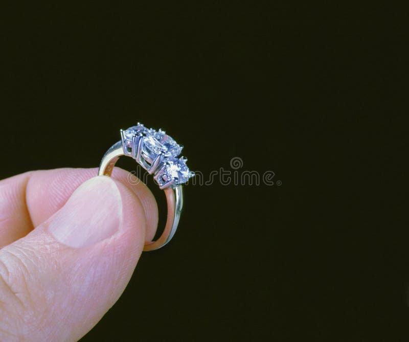 Anel de diamante da terra arrendada da mão imagem de stock royalty free