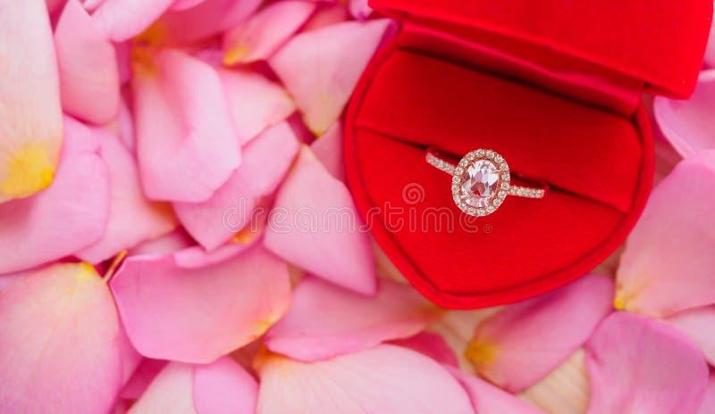 Anel de diamante elegante do casamento na guarda-joias vermelha do coração no fundo cor-de-rosa bonito da pétala cor-de-rosa fotografia de stock