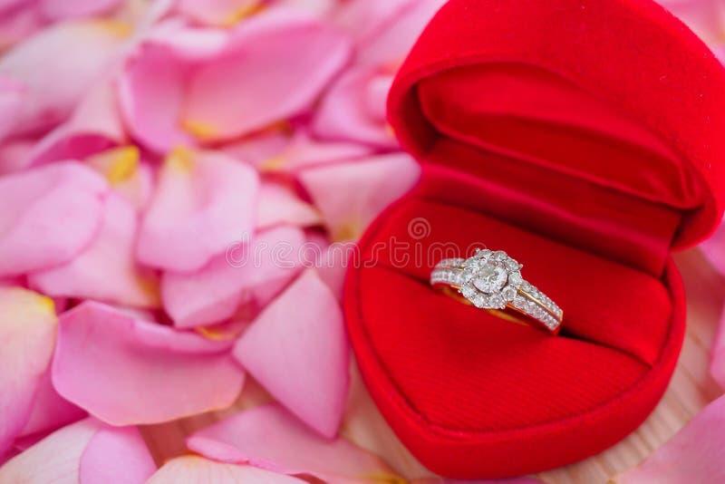 Anel de diamante elegante do casamento na guarda-joias vermelha do coração no fundo cor-de-rosa da pétala cor-de-rosa fotos de stock