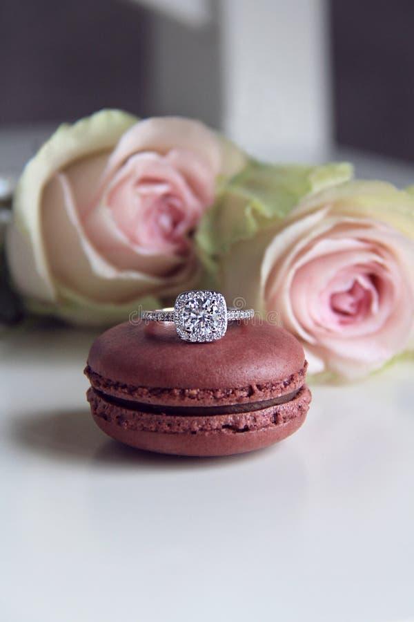 Anel de diamante no fundo do macaron e das rosas imagem de stock