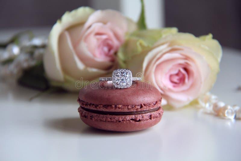 Anel de diamante no fundo do macaron e das rosas fotografia de stock royalty free